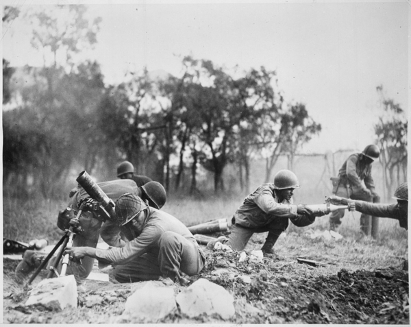 Members of a Negro mortar company of the 92nd Division pass the ammunition and heave it over at the Germans in an almos   NARA   535546